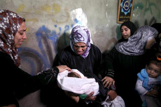 The mother of 10-month-old Hanen Tafesh, killed in an Israeli airstrike on Thursday in Gaza, mourns with family members at the baby's funeral, 16 November. Reports indicate that as of Friday, 8 children have been killed in Israeli attacks. (Majdi Fathi / APA images)