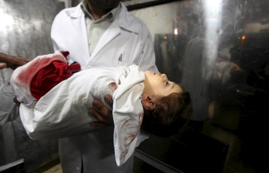 A Palestinian medic carries the body of two years-old Abdel Rahman Majdi Naim, after he was killed in an Israeli strike