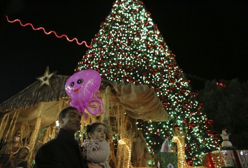 A man holds a child in front of a Christmas tree that was lit during a ceremony outside the Church of Nativity in the West Bank town of Bethlehem December 15, 2012. REUTERS/Ammar Awad