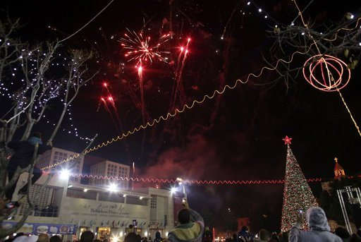 People watch fireworks explode after the lighting of the Christmas tree outside the Church of Nativity in the West Bank town of Bethlehem December 15, 2012. REUTERS/Ammar Awad