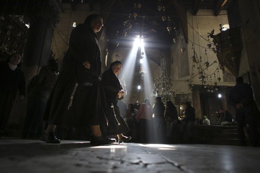 Nuns walk past worshippers in the Church of the Nativity in the West Bank town of Bethlehem December 16, 2012. REUTERS/Ammar Awad