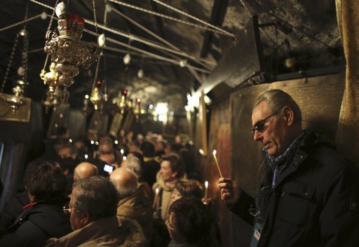 A worshipper holds a candle in the Church of the Nativity, the site revered as the birthplace of Jesus, ahead of Christmas in the West Bank town of Bethlehem December 21, 2012. REUTERS/Ammar Awad