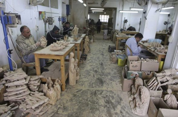 A Palestinian carpenter carves wooden statues of the Virgin Mary and Jesus in a workshop, ahead of Christmas in the West Bank town of Bethlehem December 21, 2012. REUTERS/Ammar Awad
