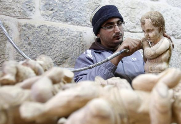 A Palestinian wood carver works on a figurine of the baby Jesus in an olive wood factory in the West Bank town of Bethlehem, ahead of Christmas, Friday, Dec. 21, 2012.