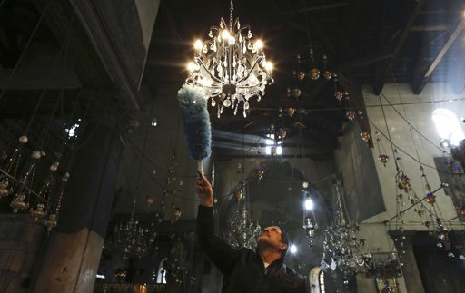 A man cleans a chandelier inside the Church of the Nativity, the site revered as the birthplace of Jesus, ahead of Christmas in the West Bank town of Bethlehem December 22, 2012. REUTERS/Ammar Awad .