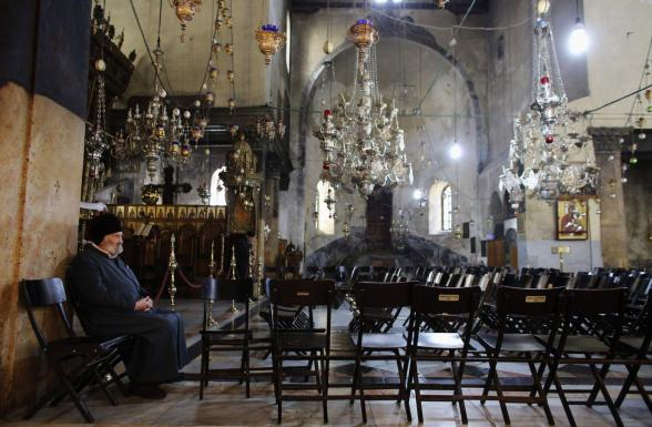 A man sits inside the Church of the Nativity, the site revered as the birthplace of Jesus, ahead of Christmas in the West Bank town of Bethlehem December 22, 2012. REUTERS/Ammar Awad