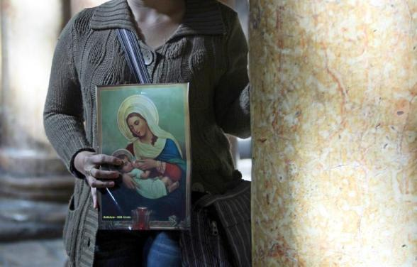 Bethlehem (-), 23/12/2012.- A Christian visitor holds an icon-style image amid the large marble columns in the central nave of the Church of the Nativity, where Christians believe the Virgin Mary gave birth to Jesus Christ, in the West Bank town of Bethlehem, 23 December 2012. EFE/EPA/ABED HASHLAMOUN