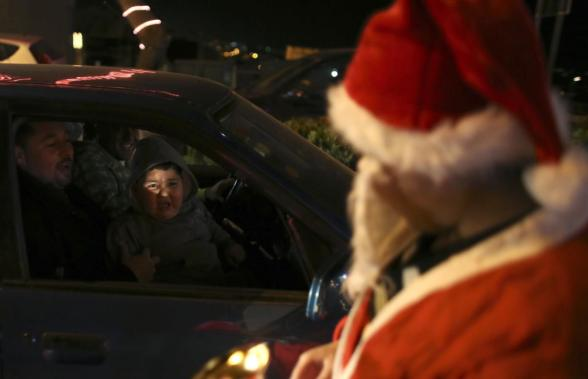 A Palestinian boy reacts to a man dressed as Santa Claus in the West Bank town of Bethlehem ahead of Christmas December 23, 2012. REUTERS/Ammar Awad
