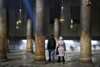 People walk inside the Church of Nativity, traditionally believed by Christians to be the birthplace of Jesus Christ, ahead of Christmas, in the West Bank town of Bethlehem, Sunday, Dec. 23, 2012. (AP Photo/Nasser Shiyoukhi) AP