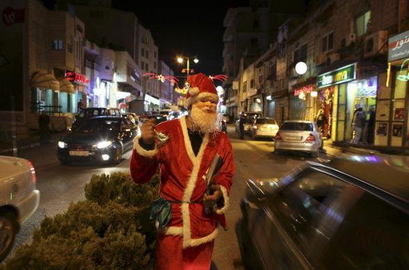 A Palestinian dressed as Santa Claus rings a bell in the West Bank town of Bethlehem ahead of Christmas December 23, 2012. REUTERS/Ammar Awad