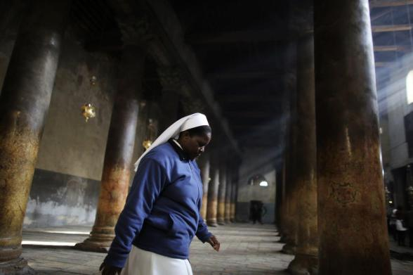 A nun walks through the Church of Nativity, the site revered by Christians as Jesus' birthplace, ahead of Christmas in the West Bank town of Bethlehem December 23, 2012. REUTERS/Ammar Awad