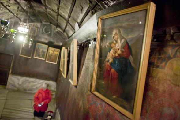 JER03. Bethlehem (-), 23/12/2012.- A Christian pilgrim prays on her knees along ancient oil paintings of Mary with the Baby Jesus in the 'Grotto,' or cave, where Christians believe the Virgin Mary gave birth to Jesus Christ, in the Church of the Nativity, in the West Bank town of Bethlehem, 23 December 2012. EFE/EPA/JIM HOLLANDER
