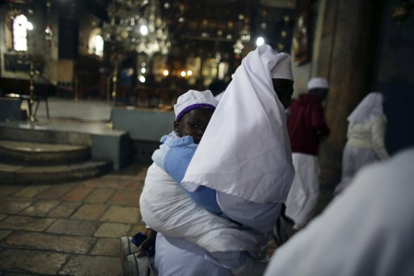 Dec 24 2012 A Nigerian pilgrim carries a child on her back as she visits Church of Nativity in Bethlehem