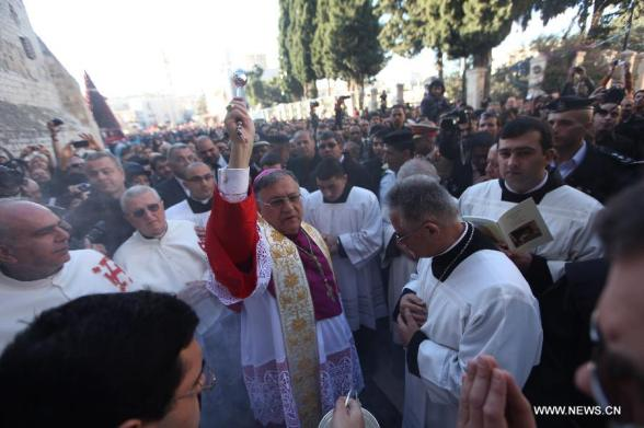 Latin Patriarch of the Holy Land Fuad Twal, head of the Roman Catholic Church in the Palestinian territories, blesses the Church of the Nativity upon his arrival to attend the Christmas celebrations in West Bank town of Bethlehem on Dec. 24, 2012. (Xinhua/Fadi Arouri)