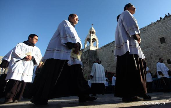 Clergymen take part in the Christmas celebrations outside the Church of the Nativity in West Bank town of Bethlehem on Dec. 24, 2012. (Xinhua/Fadi Arouri)