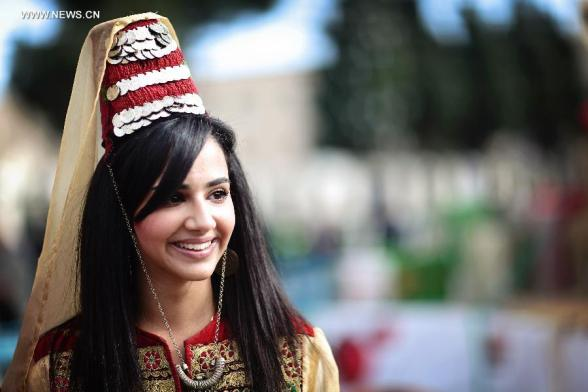A girl wearing traditional clothes smiles at the Church of the Nativity, traditionally believed to be the birthplace of Jesus Christ, as she attends the Christmas celebrations in the West Bank biblical town of Bethlehem on Dec. 24, 2012. (Xinhua/Fadi Arouri)