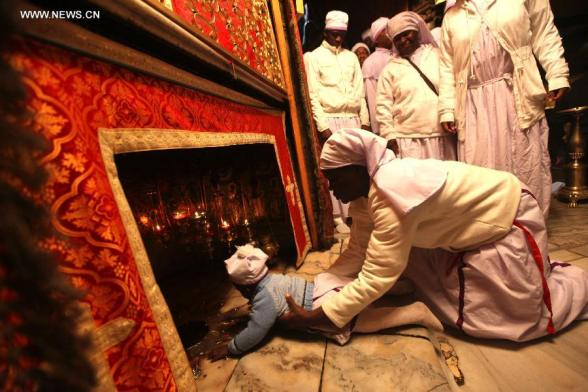 Nigerian pilgrims pray inside the Grotto in the Church of the Nativity, traditionally believed to be the birthplace of Jesus Christ, as preparations for Christmas celebrations in the West Bank biblical town of Bethlehem on Dec. 24, 2012. (Xinhua/Fadi Arouri)