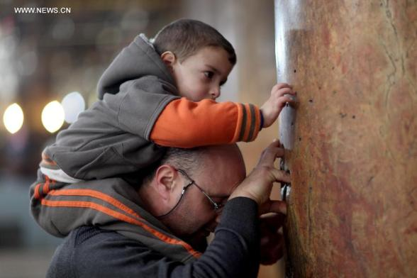 A worshiper and his son touchs a column inside the Church of the Nativity, traditionally believed to be the birthplace of Jesus Christ, as they attend the Christmas celebrations in the West Bank biblical town of Bethlehem on Dec. 24, 2012. (Xinhua/Fadi Arouri)