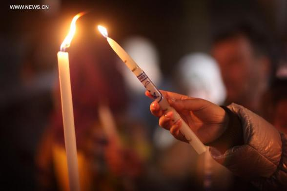 A worshiper lights a candle in the Church of the Nativity, traditionally believed to be the birthplace of Jesus Christ, as she attends the Christmas celebrations in the West Bank biblical town of Bethlehem on Dec. 24, 2012. (Xinhua/Fadi Arouri)