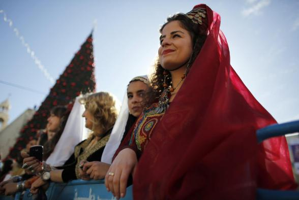 A Palestinian women dressed in traditional costume watches a Christmas parade outside the Church of Nativity in the West Bank town of Bethlehem December 24, 2012. REUTERS/Darren Whiteside