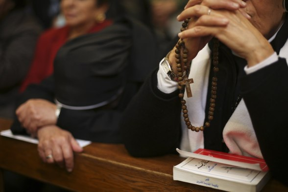 Dec 25 2012 A worshipper holds rosary beads during Catholic mass at the Church of St. Catherine in Bethlehem on Christmas day
