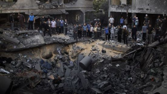 Palestinian men gather around a crater caused by an Israeli air strike on the al-Dallu family's home in Gaza City on November 18, 2012.
