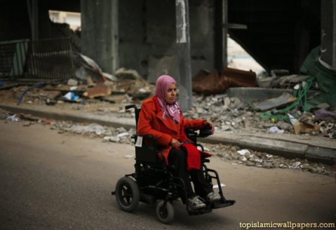 dec-4-2012-disabled-palestinian-woman-rides-wheelchair-past-a-soccer-stadium-destroyed-in-air-strike-during-an-eight-day-war-on-gaza-photo-by-suhaib-salem
