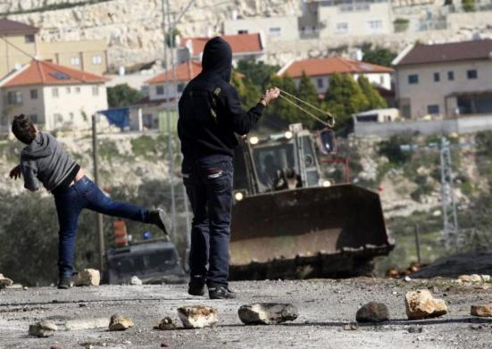 Palestinian protesters throw stones at an Israeli military bulldozer during clashes at a protest against the nearby Jewish settlement of Kdumim, in the West Bank village of Kfar Kadum, near Nablus on 18 January 2013. (Photo: Reuters – Abed Omar Qusini)