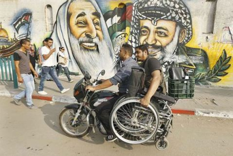 DOCU_GRUPO A wheelchair-bound Palestinian freelance photographer holds his wheelchair as he rides on a motorcycle past murals in Gaza City