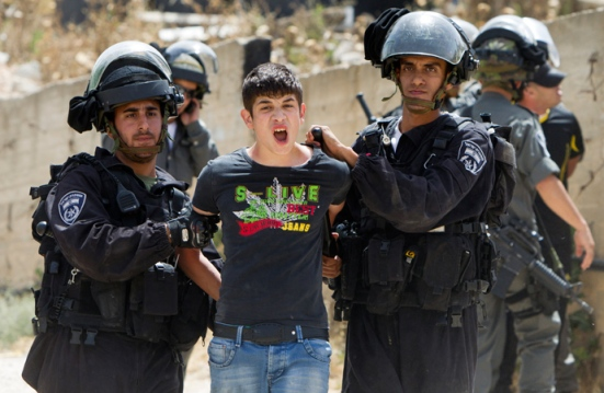 A Palestinian youth is arrested by Israeli security as bulldozers destroy a Palestinian home in Arab east Jerusalem's neighborhood of Beit Hanina, on May 29, 2013 (AFP Photo / Ahmad Gharabli)