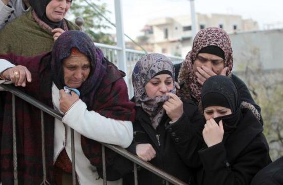 Female mourners grieve during the funeral of 14-year-old Palestinian Waji al-Ramhi in the Jelazoun refugee camp in the West Bank city of Ramallah on December 8, 2013. (AFP)