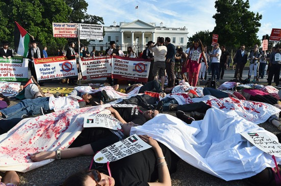Protesters lay on the street symbolizing Palestinians killed by Israel's bombing in Gaza during a demonstration in front of the White House in Washington, DC, on July 16, 2014. Israel's campaign, which entered its 10th day on Thursday, has killed 223 Palestinians so far, with a Gaza-based human rights group saying over 80 percent of them were civilians. AFP PHOTO/Jewel Samad