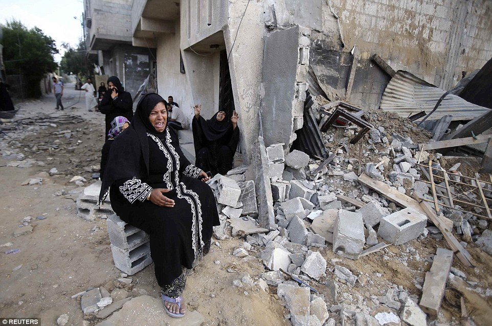 Palestinian women react next to the rubble of their relatives' house, which police said was destroyed in an Israeli air strike, in Khan Younis in the southern Gaza Strip July 21, 2014. Israeli tanks shelled militant targets in the Gaza Strip on Monday and a woman died in an air strike after the bloodiest day of a nearly two-week military offensive that showed no signs of abating, despite global calls for a truce. Palestinian health officials said the death toll since July 8 had reached 447, including many civilians, with a woman killed in the predawn strike in Beit Hanoun and 12 more bodies recovered from the embattled Shejaia neighbourhood where the number of fatalities rose to 72 from Sunday's fighting. Israel's army said it had been targeting militants from Gaza's dominant Hamas group, charging that they fired rockets from Shejaia and built tunnels and command centres there. The army said it had warned civilians to leave two days earlier.  REUTERS/Ibraheem Abu Mustafa (GAZA - Tags: