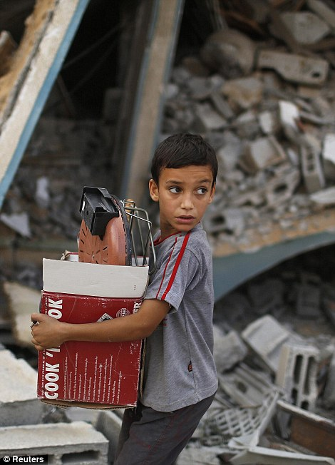 A Palestinian boy carries belongings as he walks past a house which police said was destroyed in an Israeli air strike, in Gaza City July 21, 2014. Israeli tanks shelled militant targets in the Gaza Strip on Monday and a woman died in an air strike after the bloodiest day of a nearly two-week military offensive that showed no signs of abating, despite global calls for a truce. Palestinian health officials said the death toll since July 8 had reached 447, including many civilians, with a woman killed in the predawn strike in Beit Hanoun and 12 more bodies recovered from the embattled Shejaia neighborhood where the number of fatalities rose to 72 from Sunday's fighting. Israel's army said it had been targeting militants from Gaza's dominant Hamas group, charging that they fired rockets from Shejaia and built tunnels and command centres there. The army said it had warned civilians to leave two days earlier. REUTERS/Suhaib Salem (GAZA - Tags: POLITICS CIVIL UNREST)