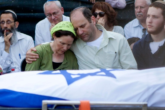 Avi and Rachel Fraenkel embrace during the funeral of their son, Naftali, a 16-year-old with dual Israeli-American citizenship, in the West Bank Jewish settlement of Nof Ayalon, Tuesday, July 1, 2014. The Israeli military found the bodies of three missing teenagers just over two weeks after they were abducted in the West Bank — a grim discovery that ended a frantic search that led to Israel's largest ground operation in the Palestinian territory in nearly a decade and drew Israeli threats of retaliation. (AP Photo/Tomer Appelbaum) ISRAEL OUT