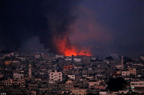 Blaze: Smoke rises from Al Shejaeiya, east Gaza City, during a military operation last night. The death toll now stands at least 550 Palestinians, health officials claim