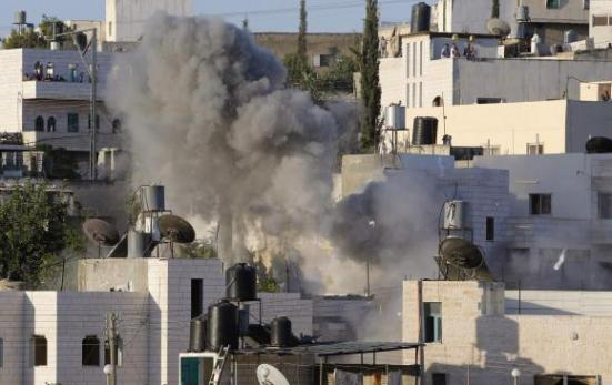 Smoke rises from the home of Palestinian Ziad Awad in the village of Idhna, close to the city of Hebron in the southern West Bank July 2, 2014.