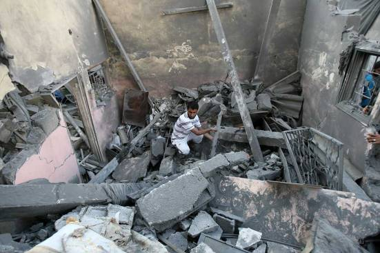 palestinian-man-inspects-wreckage-of-home-after-israeli-strike-July-2014