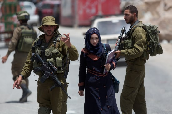 A Palestinian woman walks past Israeli soldiers at a checkpoint in the West Bank town of Hebron, on June 16, 2014, as Israel forces broadened the search for three teenagers believed kidnapped by militants and imposed a tight closure of the town. Israeli troops killed a Palestinian youth early today, as a widespread West Bank manhunt for three missing Israeli youths believed to be kidnapped entered its fourth day. AFP PHOTO/ MENAHEM KAHANA        (Photo credit should read MENAHEM KAHANA/AFP/Getty Images)