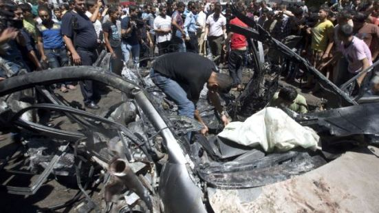 People gather around a vehicle targeted in an Israeli airstrike on Gaza City, July 8, 2014.