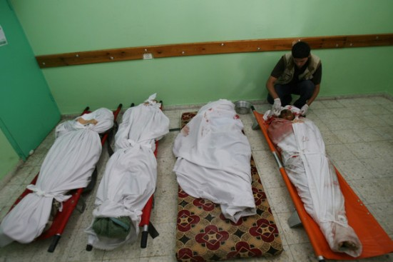 A Palestinian man tends to the bodies of four Palestinians killed in Israeli bombardment in Rafah in the southern Gaza Strip, 2 August.