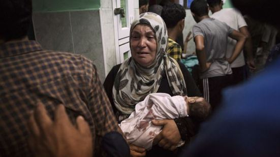 A Palestinian woman holds an infant, who was injured in an Israeli shelling at a UN-run school sheltering Palestinian refugees, at a hospital in the northern Gaza Strip on July 24, 2014.