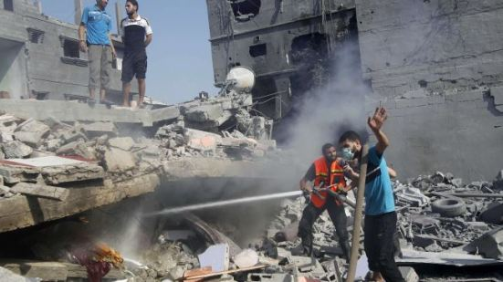 Palestinians extinguish a fire in a damaged building, which was hit in an Israeli strike, in Rafah, in the southern Gaza Strip on August 2, 2014.