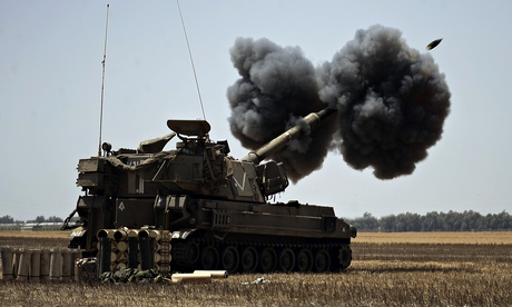 An Israeli tank near the border fires a shell towards targets in the Gaza Strip