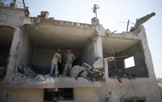 Palestinians stand in a badly damaged house as they look at rescue workers searching for for victims from under the rubble of a neighbouring house, which witnesses said was destroyed by an Israeli air strike, in Beit Lahiya in the northern Gaza Strip August 25, 2014.