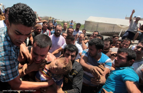 A man carries the body of a Palestinian boy whom hospital officials said was killed in an Israeli air strike on his family's house