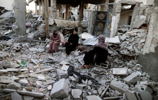 Palestinians sit outside their destroyed house in Beit Hanoun town in the northern Gaza Strip