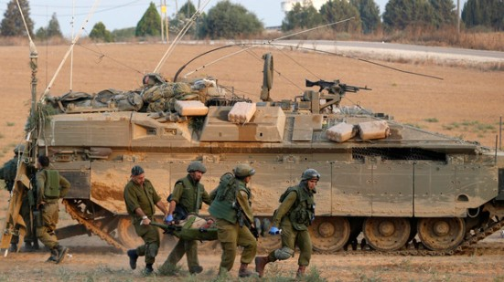 Israeli soldiers carry a comrade on a stretcher outside Gaza