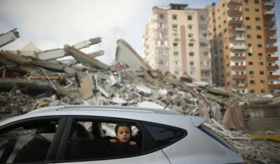 A Palestinian boy looks out a car window driving past the rubble of a residential tower, which witnesses said was destroyed in an Israeli air strike in Gaza City August 24, 2014.